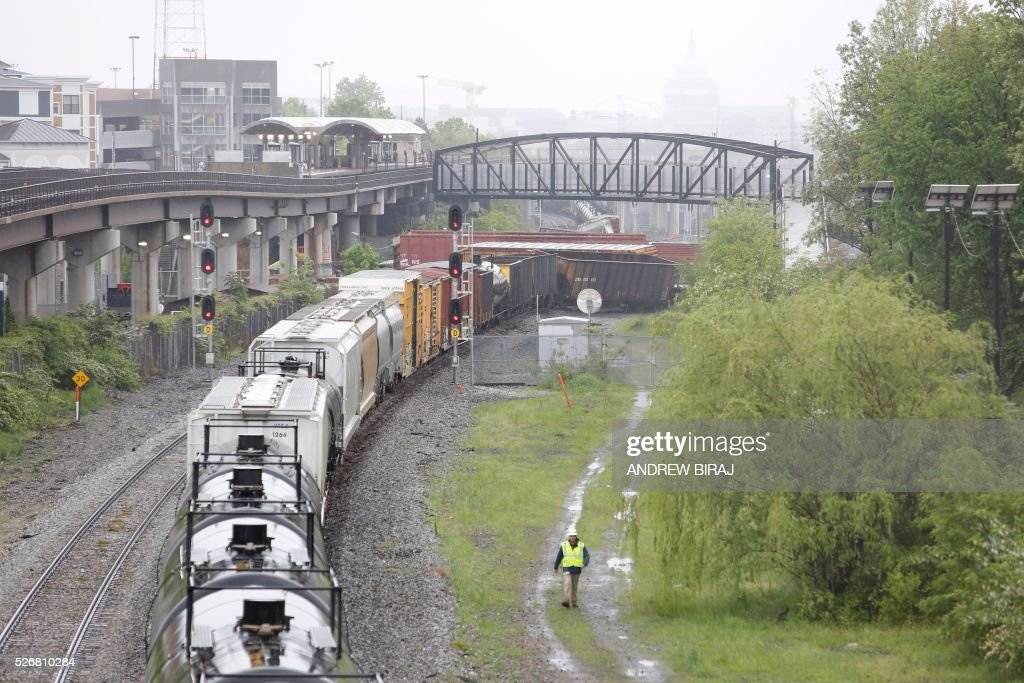 A CSX freight train is seen with several derailed cars near the Rhode Island Avenue metro station in Washington, DC, on May 1, 2016. As many as ten cars derailed from a train heading to North Carolina from Cumberland, Maryland. A leak of Sodium hydroxide was said to be leaking from a tanker, but was plugged by emergency responders and hazmat crews. / AFP / Andrew Biraj