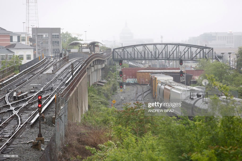A CSX freight train is seen with several derailed cars near the Rhode Island Avenue metro station in Washington, DC, on May 1, 2016. As many as ten cars derailed from a train heading to North Carolina from Cumberland, Maryland. A leak of Sodium hydroxide was said to be leaking from a tanker, but was plugged by emergency responders and hazmat crews. Sodium hydroxide is primarily used in the manufacturing of various household products including paper, soap and detergents. / AFP / Andrew Biraj