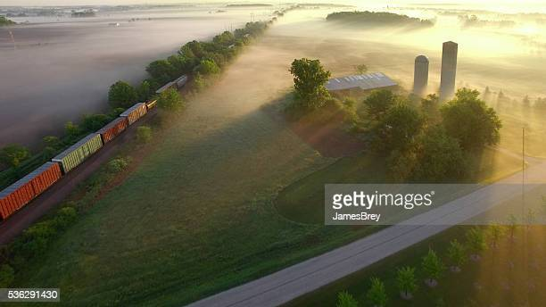 Freight train rolls across breathtaking, foggy landscape at sunrise