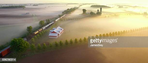 Freight train rolls across breathtakingly beautiful, foggy landscape at sunrise
