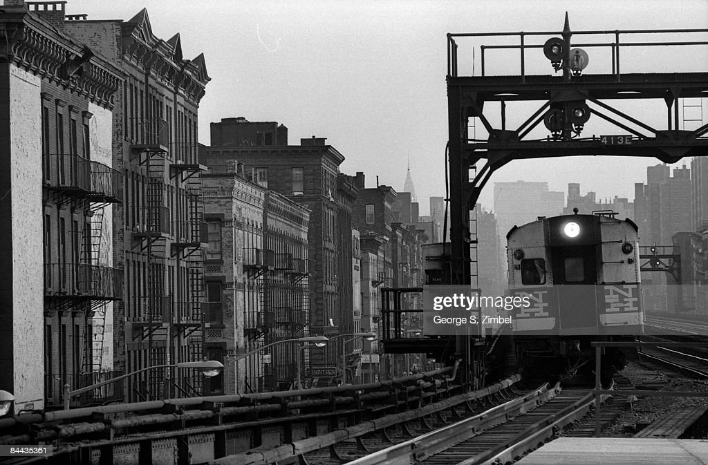 A freight train rumbles through the elevated tracks at 125th street in New York's Harlem neighborhood, 1968. `
