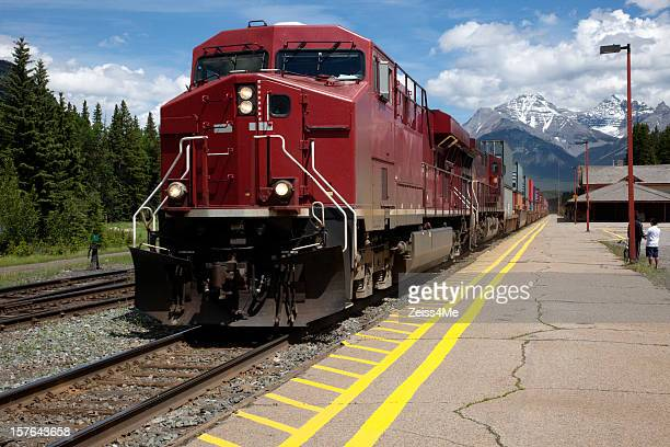 Freight train with red engine pulling out of station