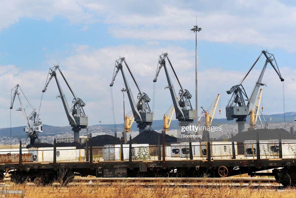 Freight wagons operated by Trainose SA stand on the dockside near cranes at Thessaloniki Port, operated by Thessaloniki Port Authority SA, in Thessaloniki, Greece, on Thursday, July 18, 2013. Russian Railways is interested in buying Thessaloniki Port and Greek rail operator Trainose SA as one single unit, newspaper Real News reported, citing an interview with the Russian company's CEO Vladimir Yakunin. Photographer: Oliver Bunic/Bloomberg via Getty Images