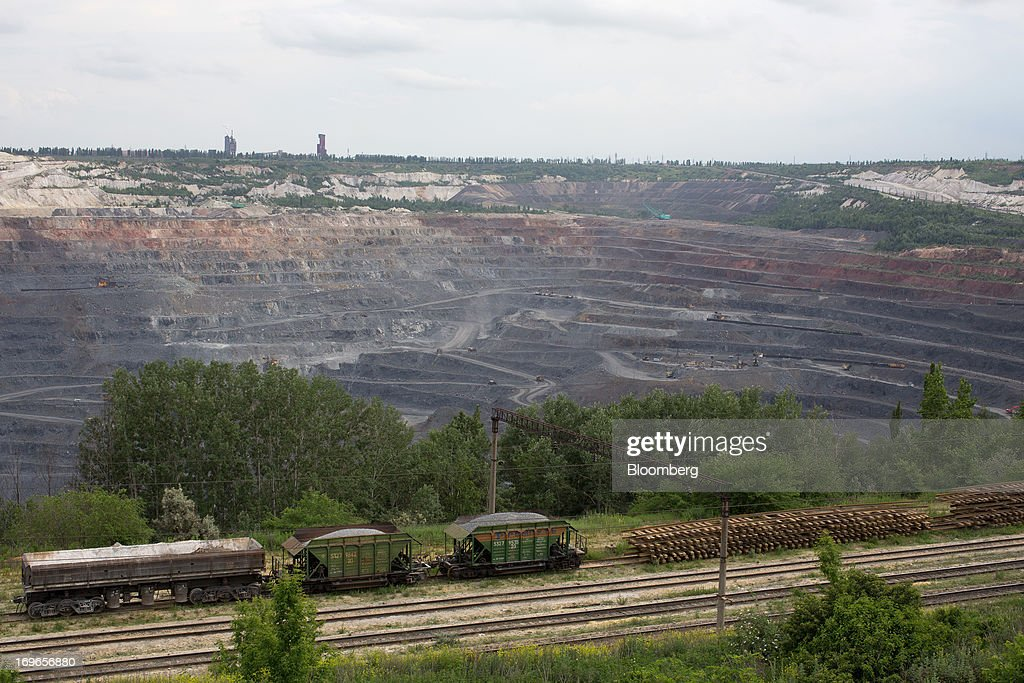 Freight wagons stand on a rail line beside the open pit of the Lebedinsky GOK (LGOK) iron ore mining and processing plant, operated by Metalloinvest Holding Co., in Gubkin, Russia, on Tuesday, May 28, 2013. Lebedinsky, Russia's third biggest iron ore mine, is owned 81 percent owned by Russian billionaire Alisher Usmanov, who also owns Mikhailovsky GOK, Russia's second-biggest iron ore mine, and Oskol Electrometallurgical Combine, a steel plant supplied by Lebedinsky. Photographer: Andrey Rudakov/Bloomberg via Getty Images