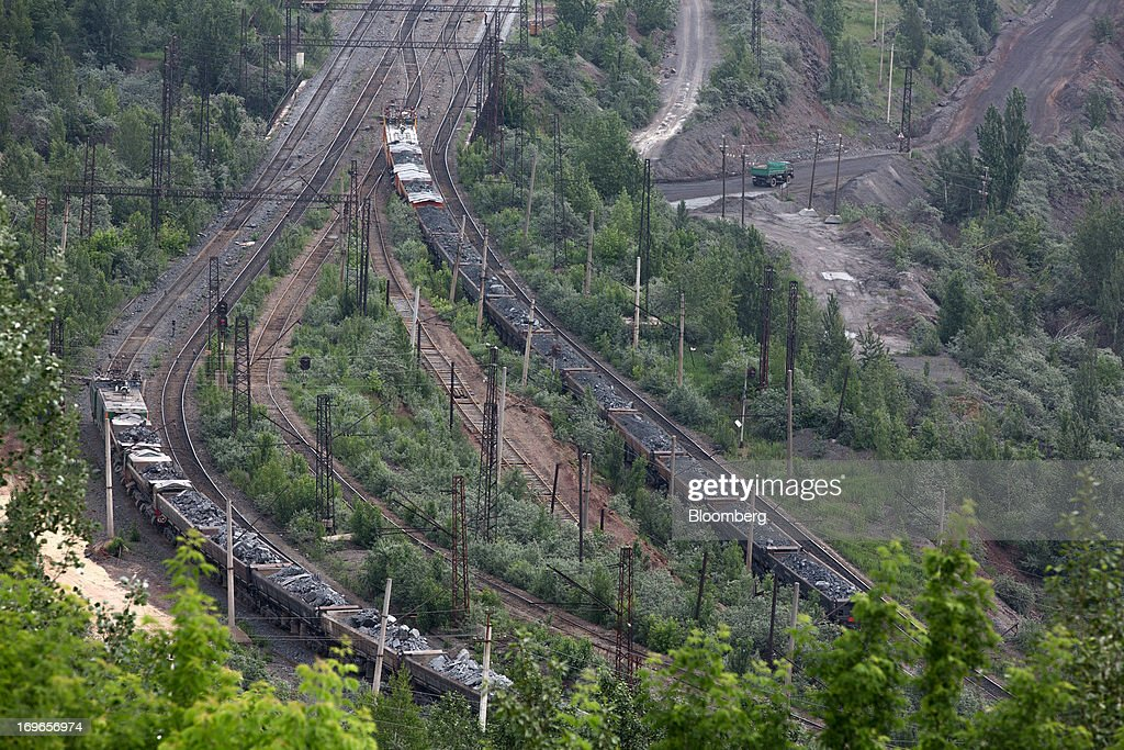 Freight wagons transport excavated rock from the open pit of Lebedinsky GOK's (LGOK) iron ore mining and processing plant, operated by Metalloinvest Holding Co., in Gubkin, Russia, on Tuesday, May 28, 2013. Lebedinsky, Russia's third biggest iron ore mine, is owned 81 percent owned by Russian billionaire Alisher Usmanov, who also owns Mikhailovsky GOK, Russia's second-biggest iron ore mine, and Oskol Electrometallurgical Combine, a steel plant supplied by Lebedinsky. Photographer: Andrey Rudakov/Bloomberg via Getty Images