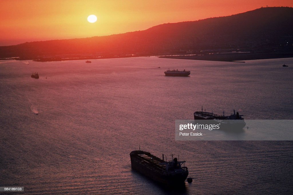 Freighters sailing into a sunset.