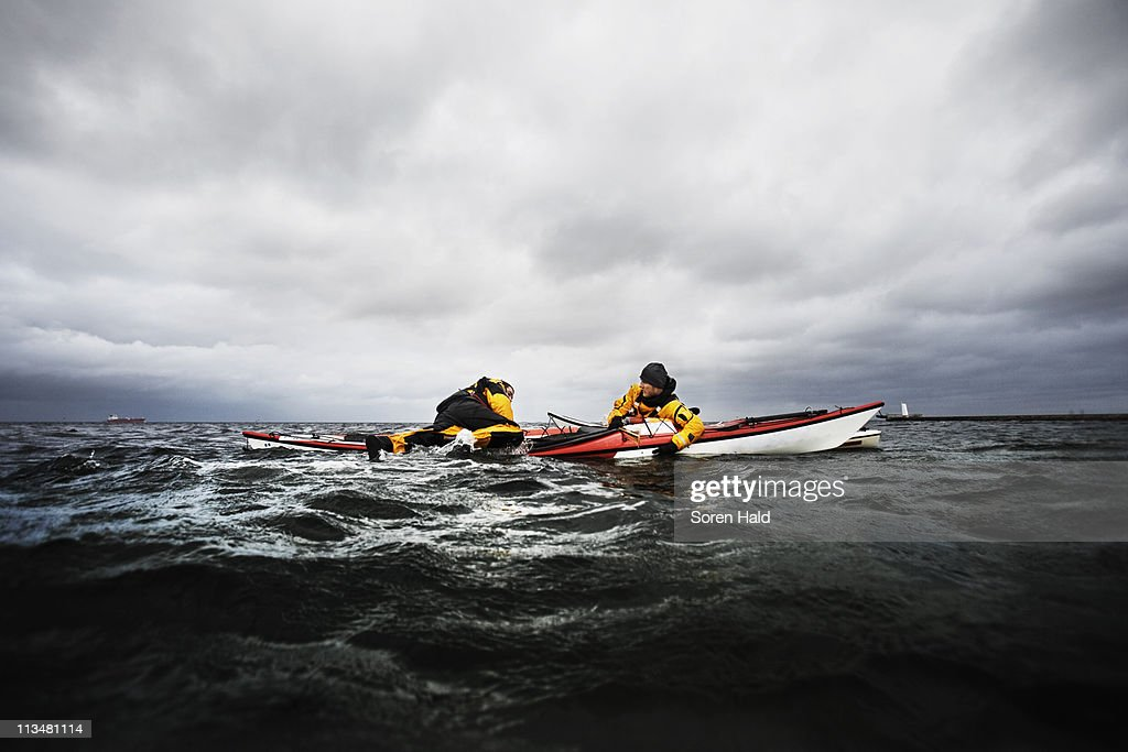 Freinds in kayak helping each other