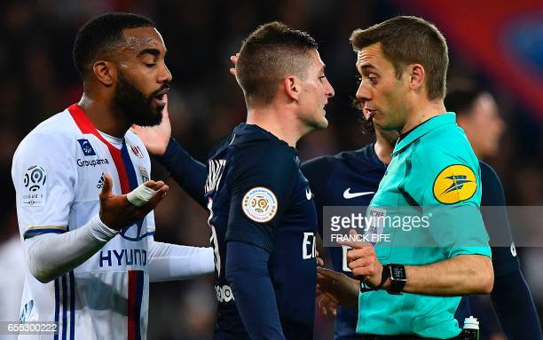 Frenc referee Clement Turpin reacts in front Paris SaintGermain's Italian midfielder Marco Verratti and Lyon's French forward Alexandre Lacazette...