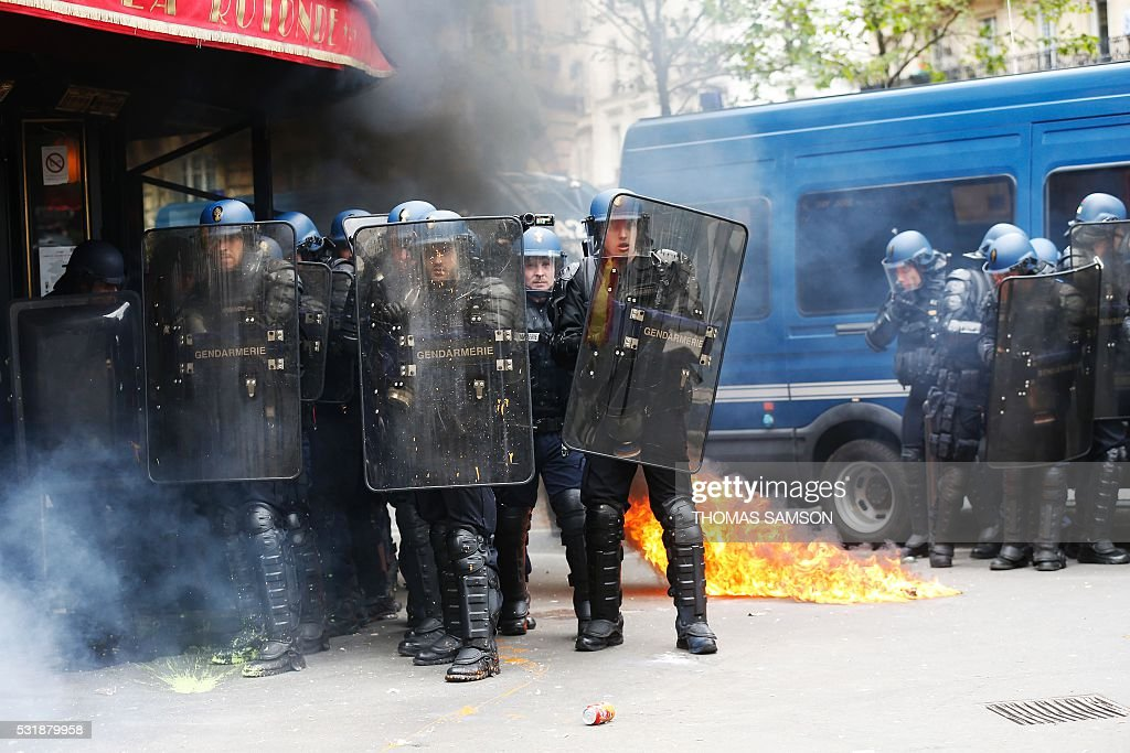 TOPSHOT Frencg gendarmes protect themselves with their shields after receiving a petrol bomb as they clash with protesters during a demonstration...