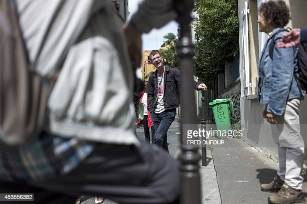 French 39yearsold homeless Vincent Rouyer laughs with tourists during a guided tour on August 9 2014 in a neighborhood of Paris Rouyer became a...