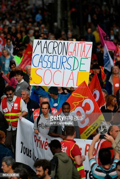 French activist JeanBaptiste Redde aka Voltuan holds a placard which translates as ' Macron and Gattaz social breakers ' marches with others during a...