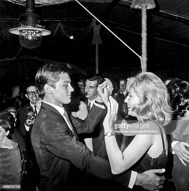 French actor Alain Delon dancing surrounded by other guests and photographers with Italian actress Monica Vitti in a club in Torvaianica on the coast...