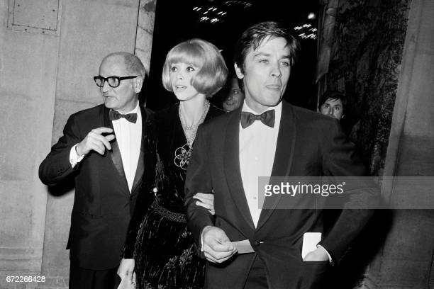 French actor Alain Delon his wife French actress Mireille Darc and Georges Cravenne leave Paris Opera House on October 15 1968 after viewing la...