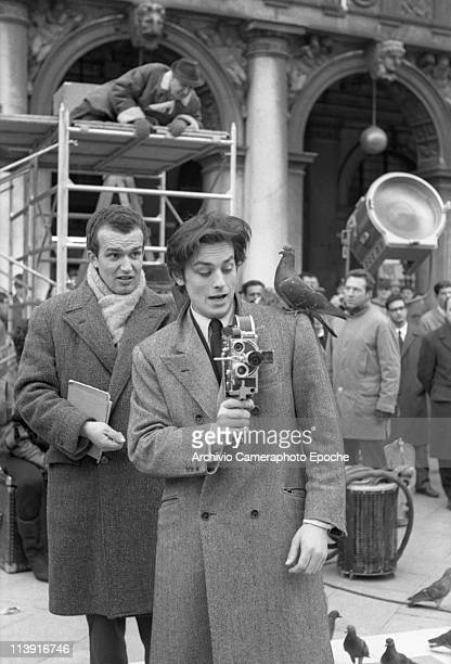 French actor Alain Delon playing with a cinecamera during the unfinished Marco Polo movie shooting in SMark Square in Venice a pigeon on his shoulder...