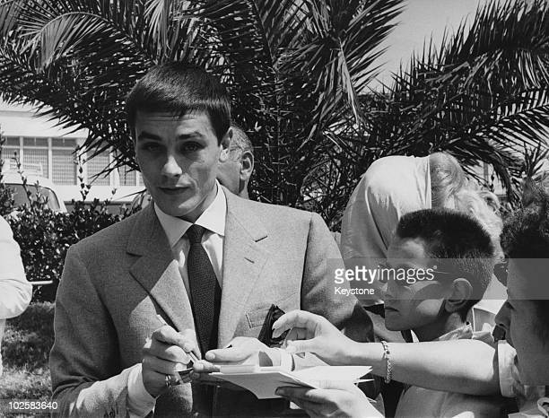 French actor Alain Delon signs autographs for young fans in Cannes during the film festival 11th May 1961