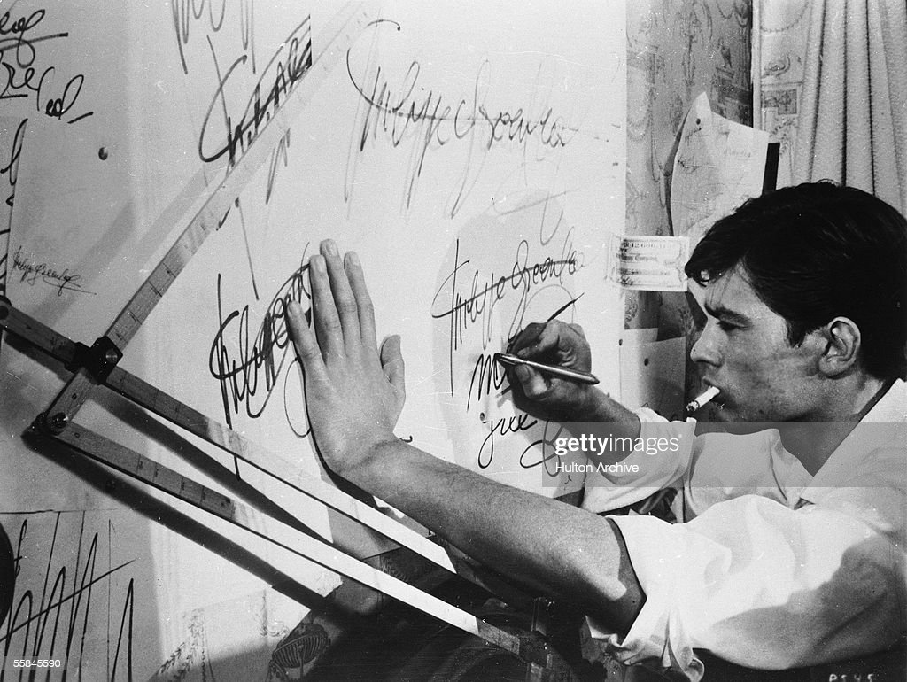 French actor Alain Delon smokes a cigarette as he practices forging a signature in a still from the film 'Purple Noon' based on the Patricia...