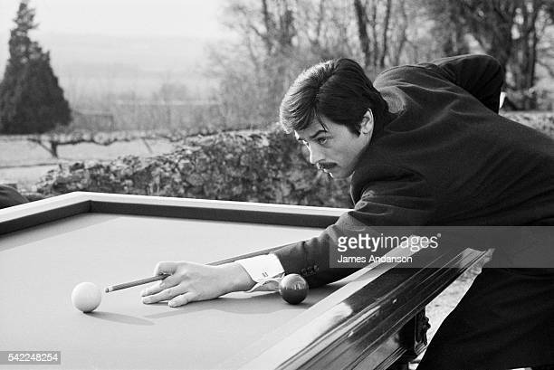 French actor Alain Delon takes a break to play a game of billards on the set of Le Cercle Rouge written and directed by JeanPierre Melville