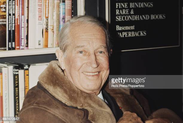 French actor and entertainer Maurice Chevalier pictured wearing a sheepskin coat as he signs copies of his autobiography 'I Remember It Well' at a...