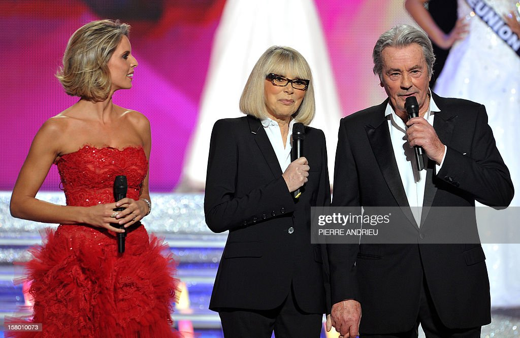 French actor and jury president Alain Delon (R) announces the final results on stage, beside (from L) former Miss France 2002 and Miss France society president Sylvie Tellier and French actress Mireille Darc, during the 66th edition of the Miss France 2013 beauty contest in the central city of Limoges on December 8, 2012. AFP PHOTO / PIERRE ANDRIEU
