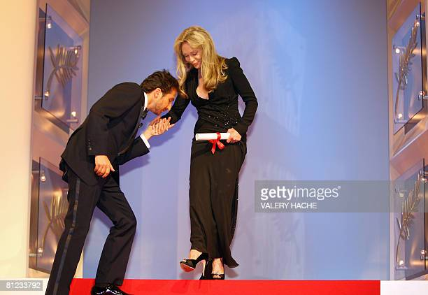 French actor and Master of Ceremony Edouard Baer kisses the hand of US actress Faye Dunaway as she arrives on stage during the Closing Ceremony of...
