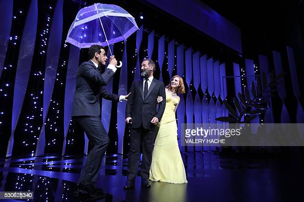 TOPSHOT French actor and Master of Ceremony Laurent Lafitte holds an umbrella on stage on May 11 2016 next to French actor Vincent Lindon and US...