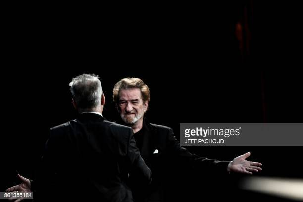 French actor and singer Eddy Mitchell cheers Louis Lumiere Institute's director Thierry Fremaux as he arrives on stage for the opening ceremony of...