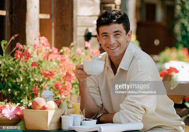 French actor and singer Patrick Bruel relaxes on a patio while vacationing in Megeve France