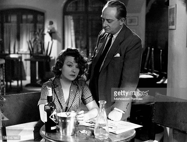 French actor and stage director Jean Debucourt holding his hand on the shoulder of French actress Edwige Feuillère sitting at a table in the film The...