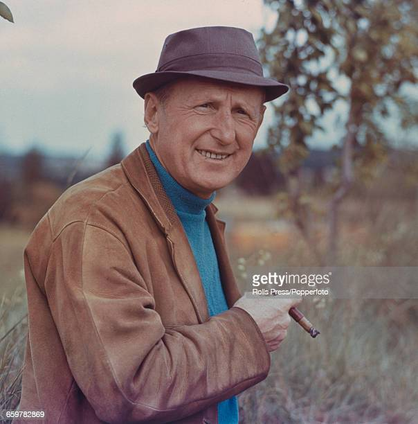 French actor Andre Bourvil who appears in the film 'Monte Carlo or Bust' posed smoking a cigar circa 1965