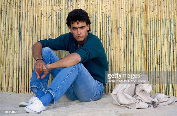 French actor Anthony Delon sits in the sand He was in Cannes to attend the 40th Cannes Film Festival