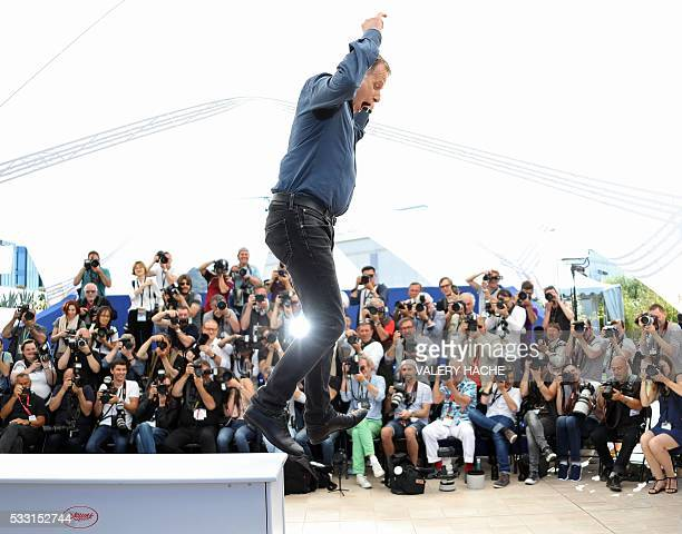 French actor Charles Berling jumps from the podium while posing on May 21 2016 during a photocall for the film 'Elle' at the 69th Cannes Film...