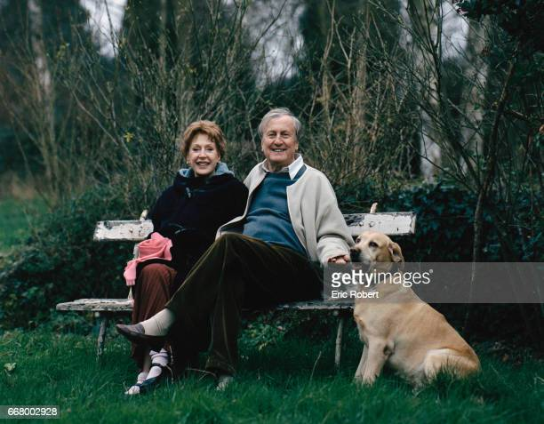 French actor Claude Rich sits on a bench with his wife Catherine and their pet dog