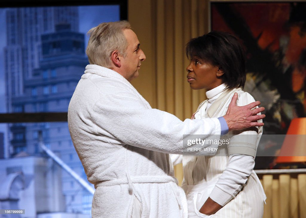 French actor Eric Debrosse, acting as former French International Monetary Fund (FMI) Director Dominique Strauss-Kahn, and Jelle Saminnadin playing Guinean Nafissatou Diallo (R), the New York Sofitel hotel housemaid, perform on November 21, 2012 the play of French Guillaume Landrot at the Paris Daunou Theater. Strauss-Kahn had been the favorite to win the May 2012 French presidential elections until May 2011, when he was arrested in New York and charged with sexually assaulting Diallo. AFP PHOTO PIERRE VERDY