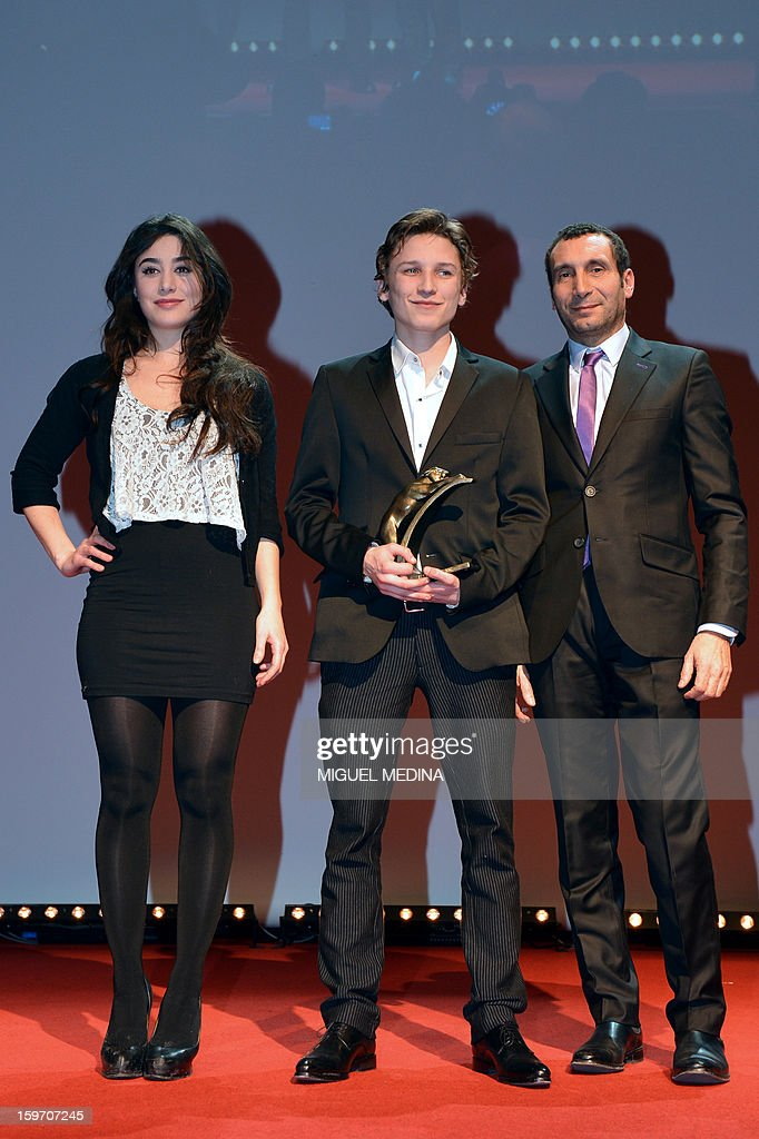 French actor Ernst Umhauer (C) poses next to French actor Zinedine Soualem (R) after receiving the most promising actor award during the 18th Lumieres awards ceremony, on January 18, 2013 at the Gaite Lyrique in Paris. International media journalists based in Paris from around 50 countries vote each year to award their own prizes to members of the French and francophone film industry. The Academy of the Lumieres paid this year a tribute to foreign actresses in French cinema and organised for the first time, the day before, the 'Francophone meetings' with hosted Tunisia, during which Tunisian director, Ferid Boughedir gave a masterclass. AFP PHOTO MIGUEL MEDINA