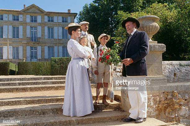 French actor Georges Wilson offers roses to welcome new family composed of French actors Nathalie Roussel Philippe Caubere 11yearold Julien Ciamaca...