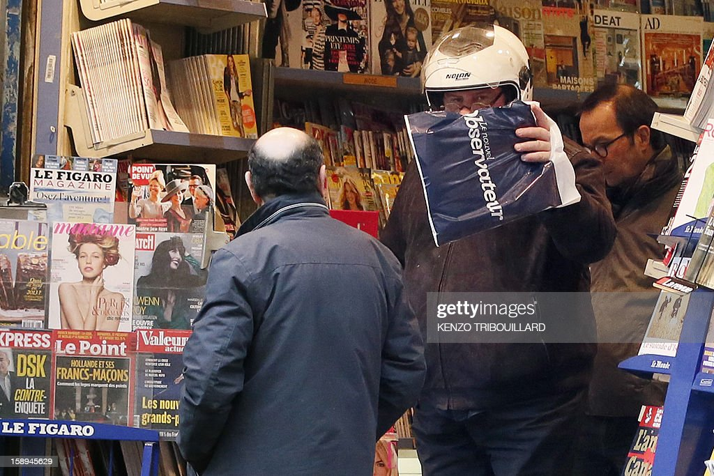 French actor Gerard Depardieu (C) hides his face as he leaves a bookshop on January 04, 2013 in Paris. Russians reacted today with amusement, disbelief and a heavy dose of irony to the news that the Kremlin has granted citizenship to French actor Gerard Depardieu to solve his tax woes.