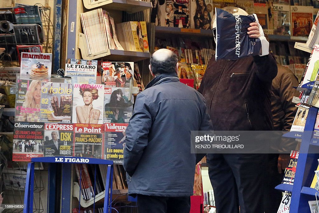 French actor Gerard Depardieu (R) hides his face as he leaves a bookshop on January 04, 2013 in Paris. Russians reacted today with amusement, disbelief and a heavy dose of irony to the news that the Kremlin has granted citizenship to French actor Gerard Depardieu to solve his tax woes. AFP PHOTO / KENZO TRIBOUILLARD