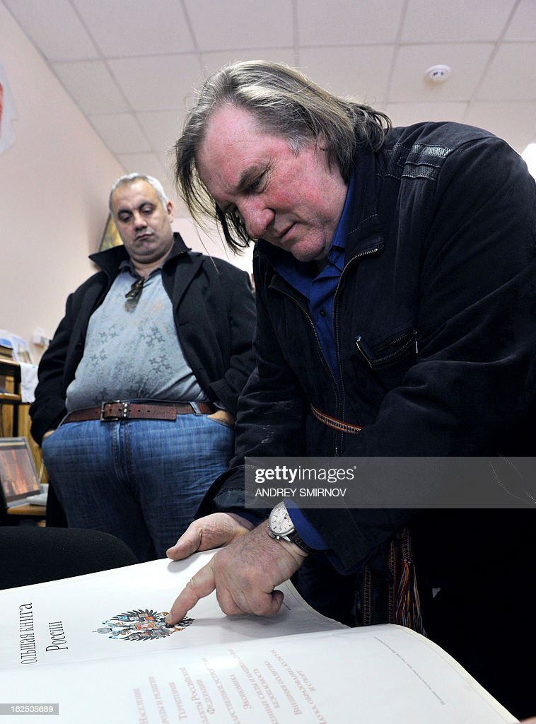 French actor Gerard Depardieu looks at the book of Russia's history as he visits the Mordovian national culture center in the village of Staraya Terizmorga outside Saransk, on February 24, 2013. Newly-minted Russian citizen Gerard Depardieu on Saturday formally registered as resident of the little-known Russian region of Mordovia, giving his residence as No. 1, Democracy Street. Depardieu was given citizenship by Putin in early January after he squabbled with French Prime Minister Jean-Marc Ayrault, who scolded his 'pathetic' decision to become a tax exile in Belgium.