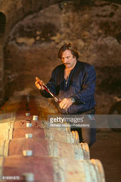 French actor Gerard Depardieu measures out red wine for tasting in the wine cellar on his vineyard | Location Tigne France