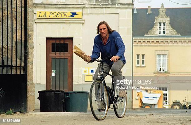 French actor Gerard Depardieu riding a bike through his vineyard | Location Tigne France