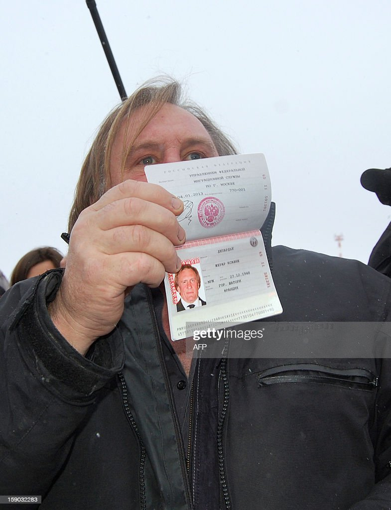 French actor Gerard Depardieu, who has threatened to quit his homeland to avoid higher taxes, shows off his new Russian passport on January 6, 2013 at Mordovia airport in Saransk where he has been offered residence in this central Russia region known for Stalin-era Gulag labour camps. The former Oscar nominee travelled to snow-covered Mordovia a day after he met with strongman President Vladimir Putin at his sumptuous Black Sea villa in the resort town of Sochi for friendly banter over a meal. AFP PHOTO / CAROLINE LARSON