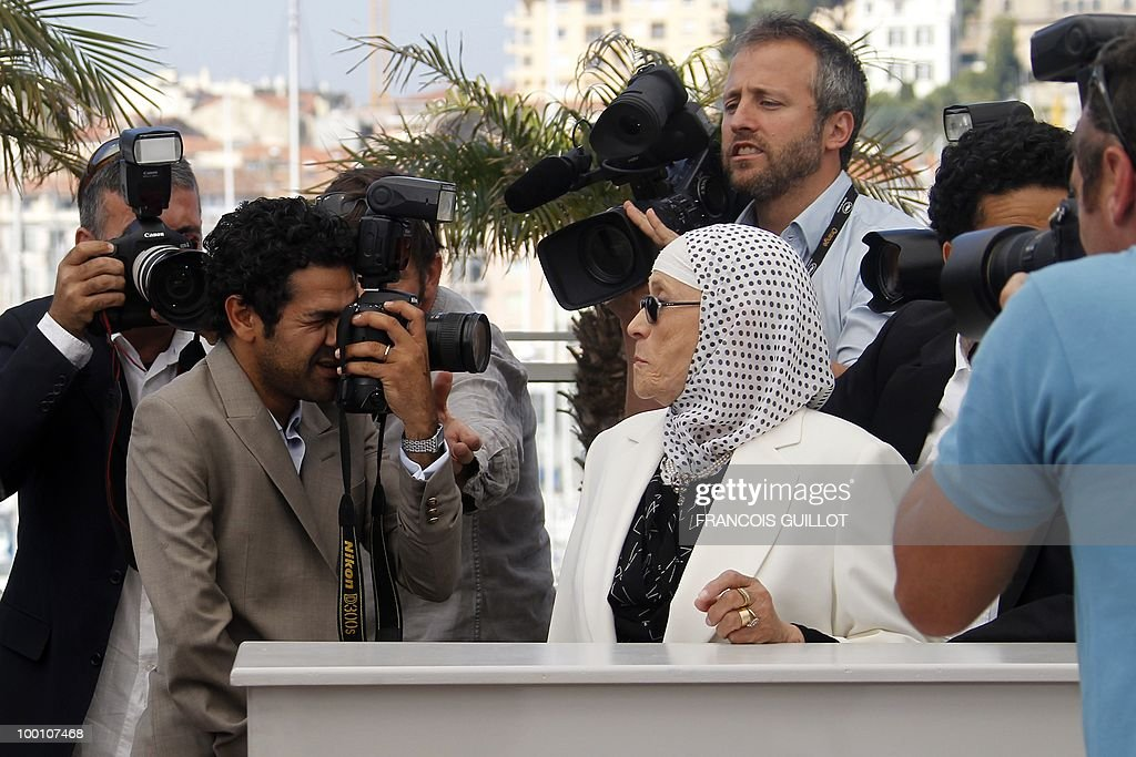 French actor Jamel Debbouze (C) pretends to take picture of actress Chafia Boudraa (C) as she poses during the photocall of 'Hors La Loi' (Outside of the Law) presented in competition at the 63rd Cannes Film Festival on May 21, 2010 in Cannes.