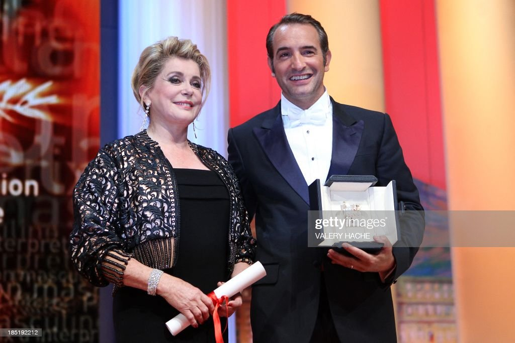 French actor Jean Dujardin poses next to French actress Catherine Deneuve after being awarded with the Prix de l'Interpretation Masculine (best actor) with the movie 'The Artist' during the closing ceremony of the 64th Cannes Film Festival on May 22, 2011 in Cannes.