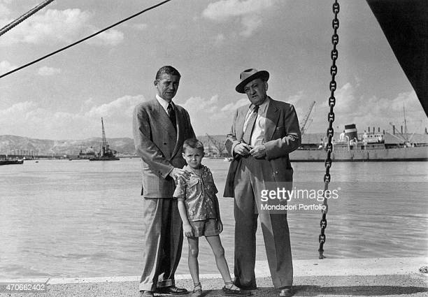 'French actor Jean Servais as Marc Hourtin and little Patrice Bergerac as Hourtin's son pose on the dock of Marseille next to Yves Deniaud as chief...