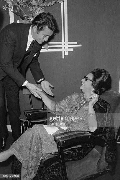 French actor JeanClaude Pascal congratulates Egyptian singer Umm Kulthum on November 14 1967 after her concert at the Olympia concert hall in Paris...