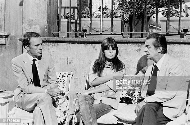French actor JeanLouis Trintignant and his daughter actress Marie Trintignant chat with Italianborn singer and actor Serge Reggiani on the set of the...