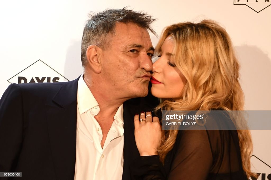 French actor Jean-Marie Bigard kisses his wife Lola Marois as they pose during the photocall for the premiere of the film 'Chacun Sa Vie' in Paris on March 13, 2017. The film is directed by French ...