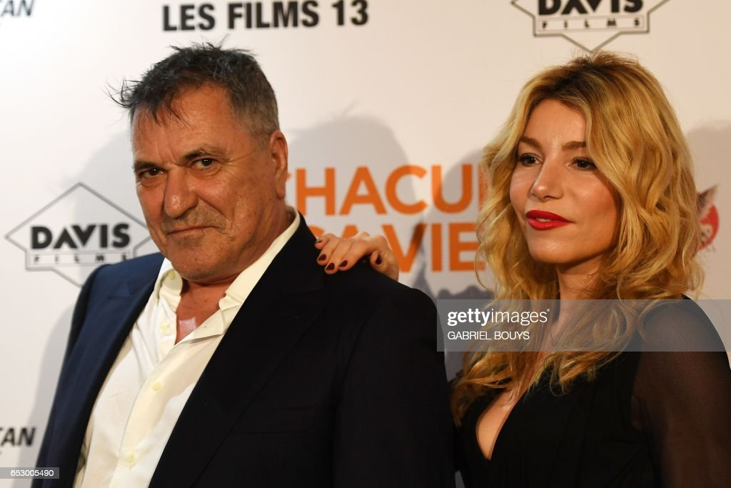 French actor Jean-Marie Bigard poses with his wife Lola Marois during the photocall for the premiere of the film 'Chacun Sa Vie' in Paris on March 13, 2017. The film is directed by French director Claude Lelouch. /