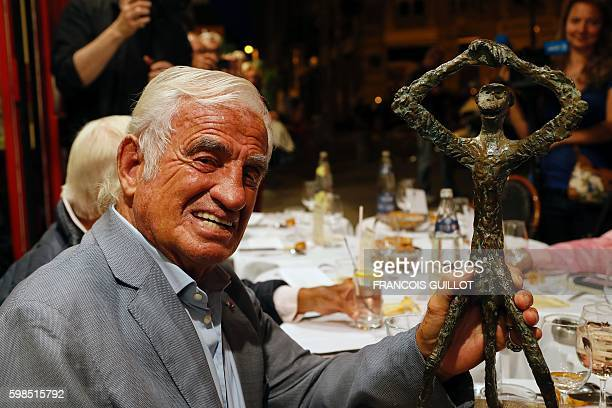 French actor JeanPaul Belmondo poses with his trophy after being awarded of the 'Prix du singe' in reference to the movie 'Un Singe en Hiver' and in...