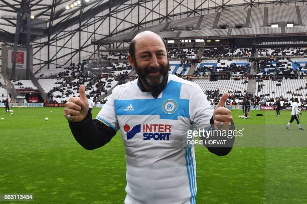 French actor Kad Merad poses in a jersey of the Olympique of Marseile as he attends the French L1 football match Olympique of Marseille vs Dijon at...